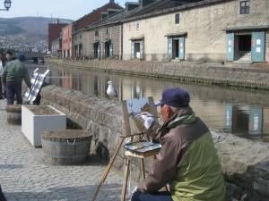 老人作畫邊餵食海鷗,海鷗還會跳到他的帽子上停留